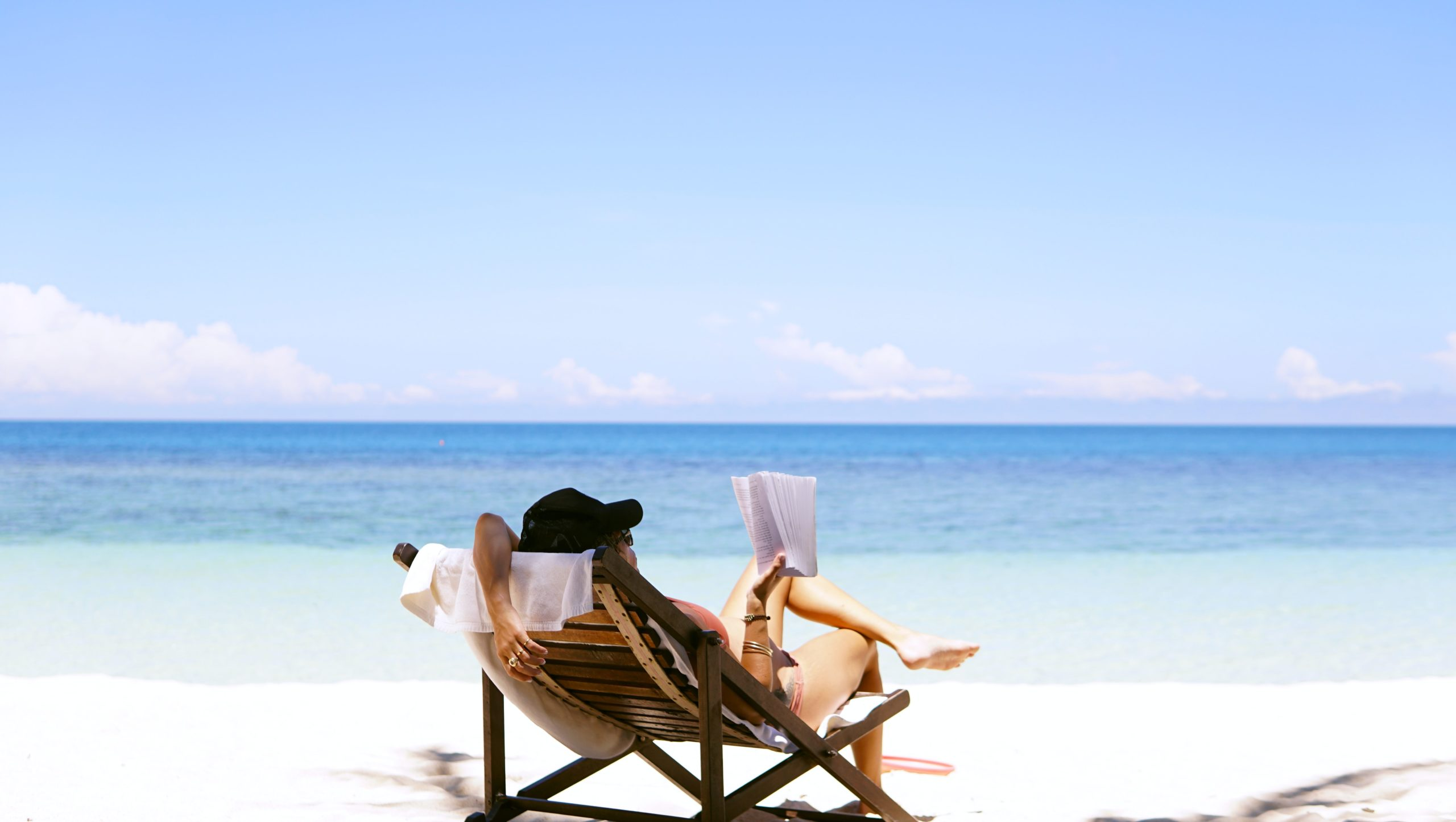 ragazza che legge un libro in spiaggia